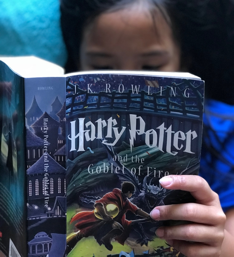 My little sister reading Harry Potter and the Goblet of Fire. She's at the point where she can read the books now, and she was influenced by me.