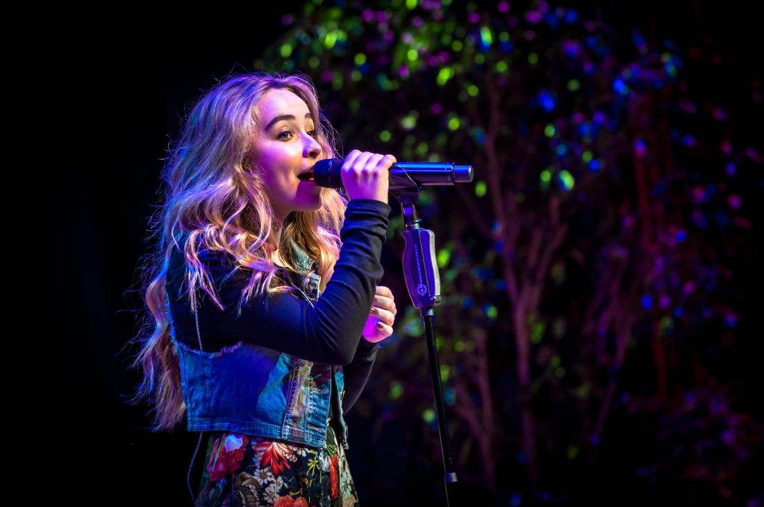 Sabrina Carpenter at a microphone