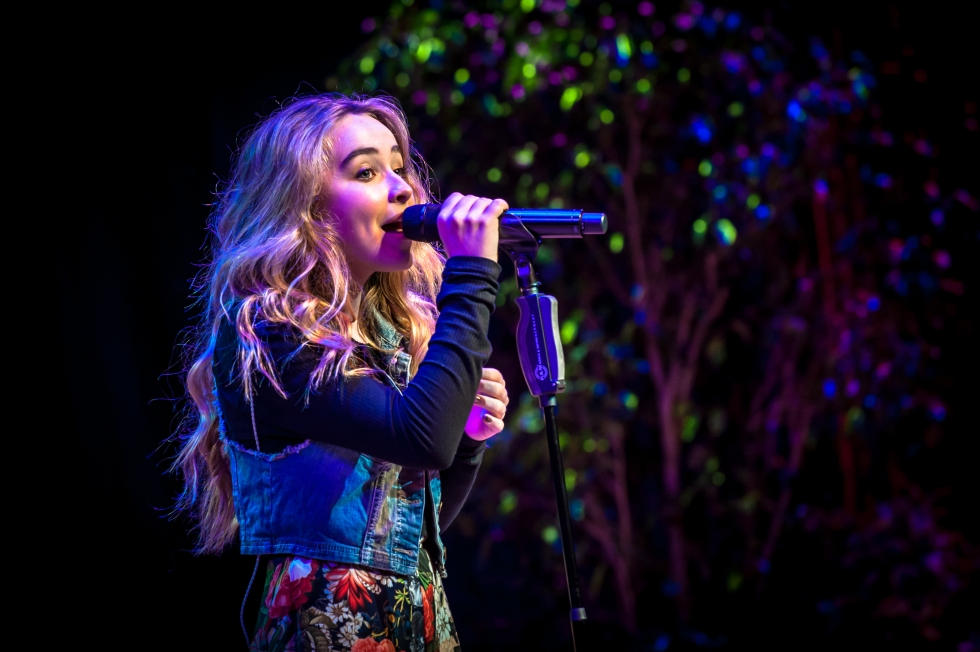 Sabrina Carpenter at a microphone