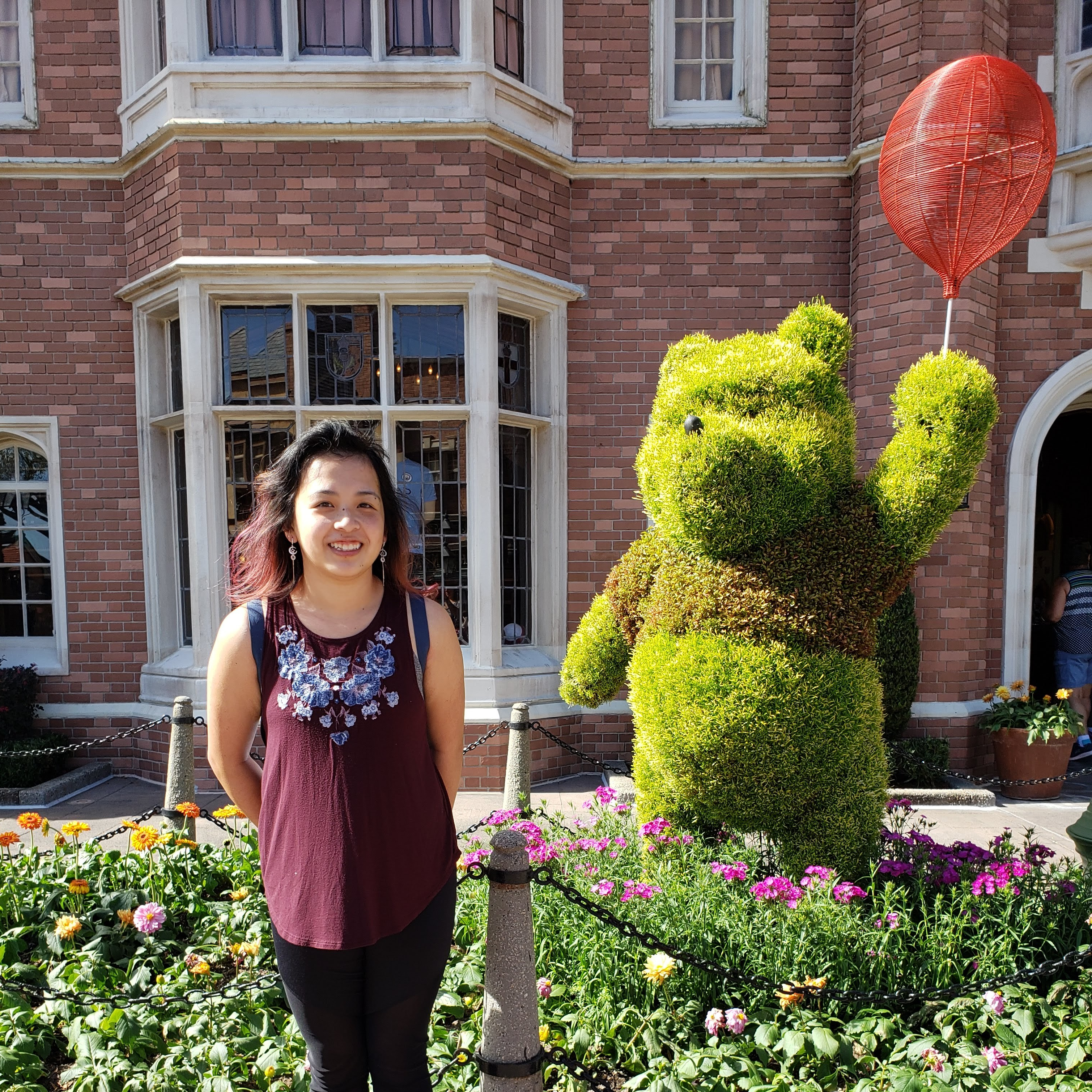 A photo of me and a Pooh Bear topiary in the London area of Epcot.