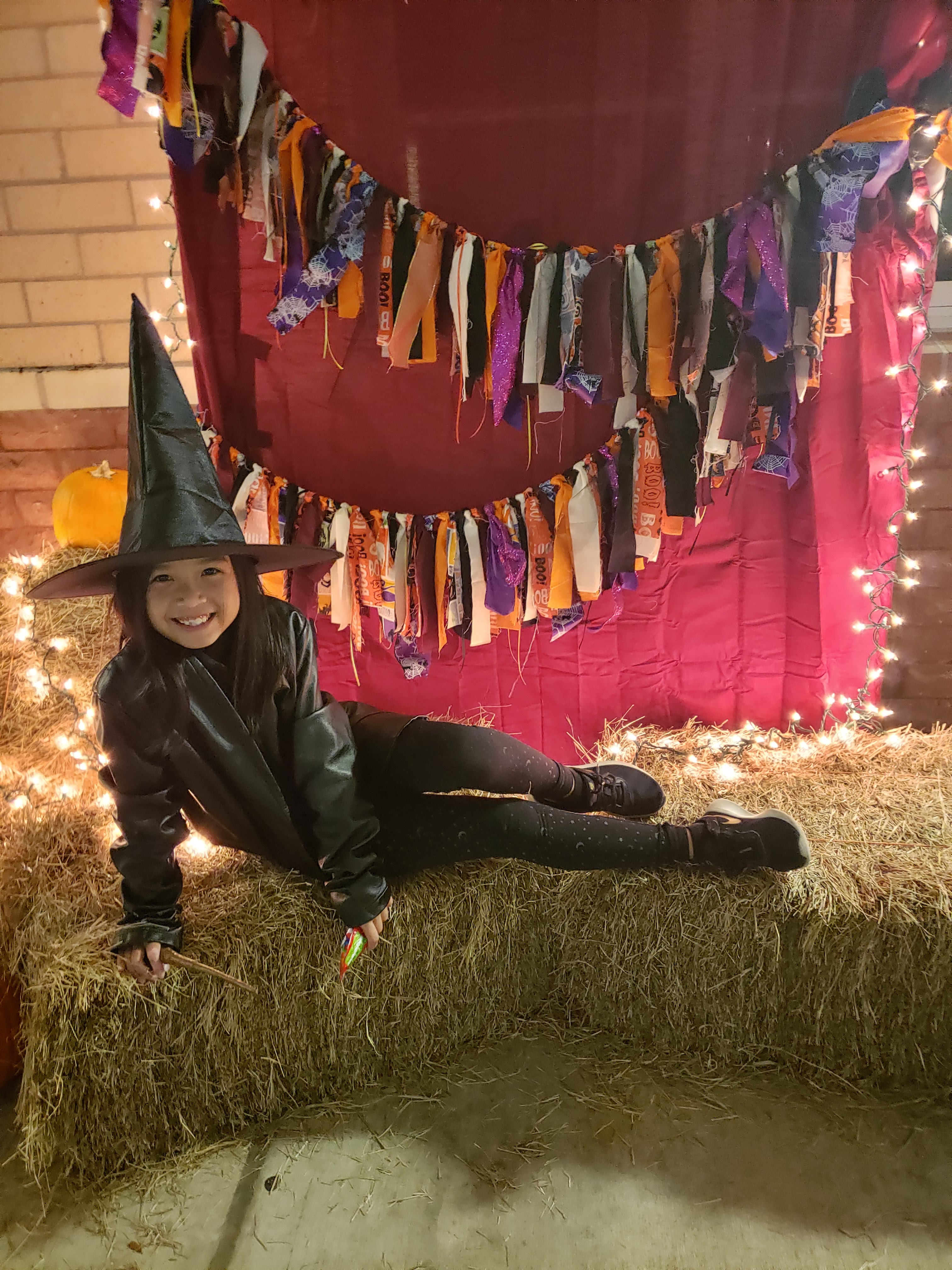 A photo of Kimmy from when she dressed up as a witch one year. She looks really happy on this bale of hay.